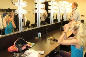 Sam and Sara Ward, the stars of INTERVAL, preparing before the show. INTERVAL is set in the late 80s. Tease those bangs, Sara!
